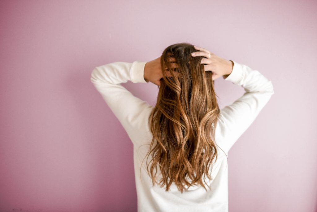 A woman in a white long-sleeve shirt stands in front of a pink wall. Photo by Element 5 Digital.