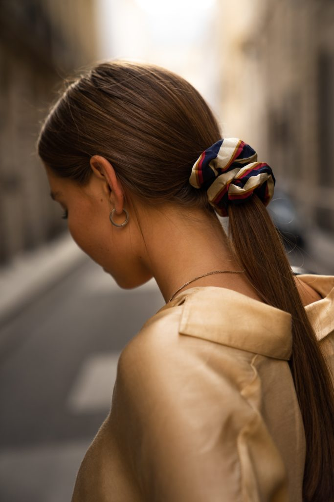 A woman with light brown hair wears a striped scrunchie hair tie.